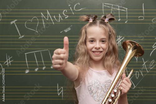 Cuadros en Lienzo Ein Mädchen mit Trompete hält Daumen hoch