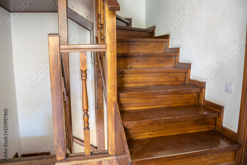 A wooden staircase to the second floor is  in a country house.