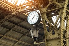 Vintage Clock And Lantern On Train Station With Building Roof.