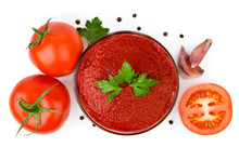 Tomato Paste In A Glass Plate, Tomatoes, Garlic And Pepper On A White Background. The View From The Top.