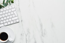 Business Composition With White Computer Keyboard, Cup Of Coffee And Eucalyptus Plant On White Marble Background. Concept Of Coffee Break At The Office. Top View With Copy Space For Text.