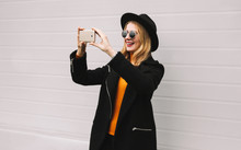 Fashion, Technology And People Concept - Stylish Smiling Woman Taking Selfie Picture By Smartphone, Elegant Female Model In Black Jacket Coat, Round Hat In City On Gray Wall Background