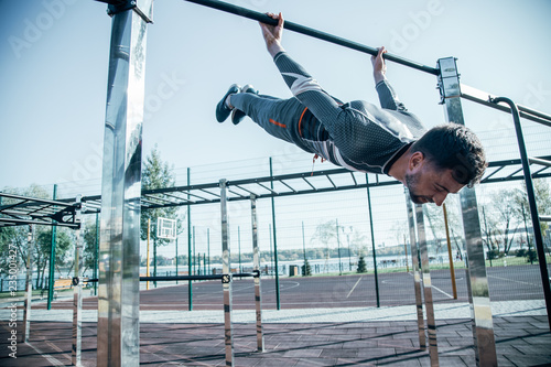 Calm sportsman hanging from the chin up bar and closing his eyes
