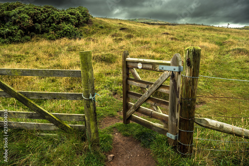 Open Wooden Gate In Fence With Rocky Trail To Grassy Pasture
