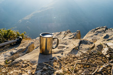 A Metal Mug Stands On The Edge Of The Cliff, Against The Background Of High Mountains, In The Rays Of The Sun