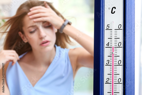 fototapeta na szkło Extreme high temperature on thermometer and woman suffering from heat