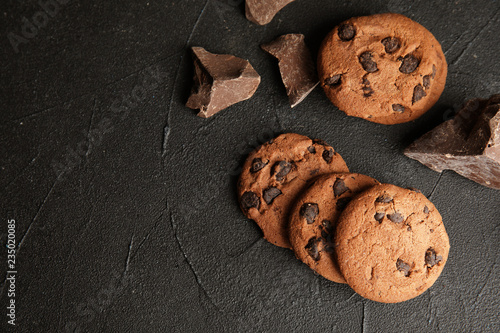Tasty chocolate chip cookies on dark background, flat lay. Space for text