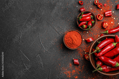 Foto auf Gartenposter Hot Chili Peppers Flat lay composition with powdered and raw chili peppers on dark background. Space for text