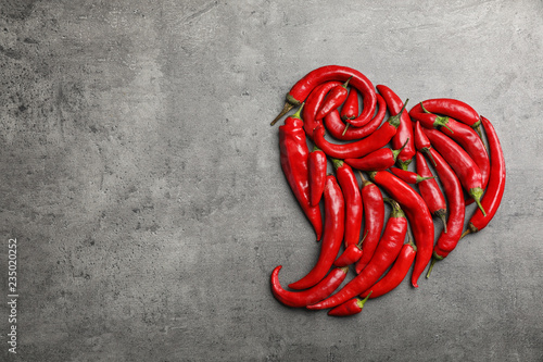 Foto op Plexiglas Hot chili peppers Heart shape made of red chili peppers on gray background, top view with space for text