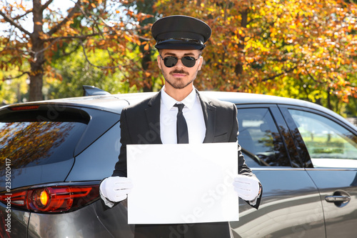 Fotografía  Young handsome driver with blank placard near car outdoors