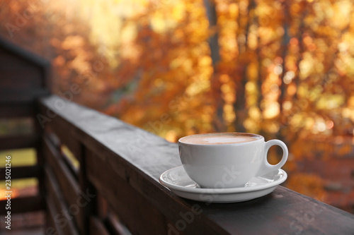 Hot cozy drink in cup on wooden railing at balcony. Space for text