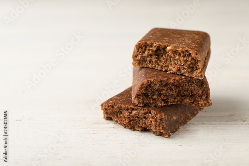 Pieces of tasty protein bar on white table. Space for text