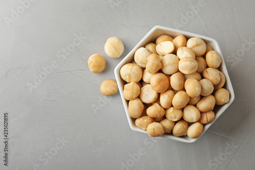 Bowl with shelled organic Macadamia nuts and space for text on grey background, top view