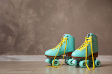 Vintage Roller Skates On Floor Near Brown Wall. Space For Text