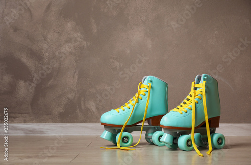 Vintage roller skates on floor near brown wall. Space for text Fototapet