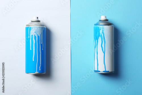 Used cans of spray paint on color background, flat lay