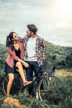 Happy Young Couple Ride Bicycle On The Hills.