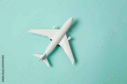 Fényképezés  Simply flat lay design miniature toy model plane on blue pastel colorful paper trendy background
