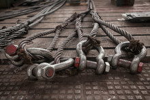 Hoist Chains, Chain Hook Wheel Alignment, Chain Hoists For Heavy Lifting, Tow Black Crane Hooks On A Floor With White Dust Of Construction Site