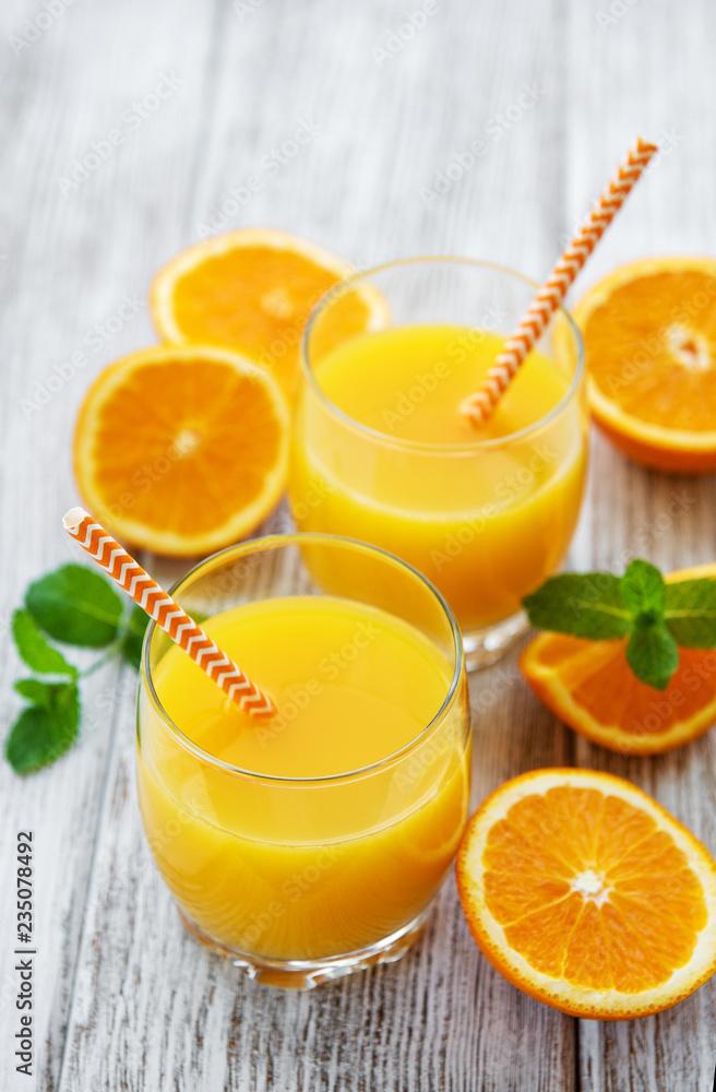 Fototapeta Glasses of juice and orange fruits