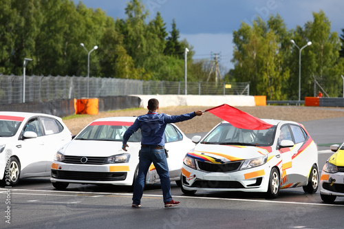 Fotografie, Tablou  Starter gives the go-ahead red flag to start car racing