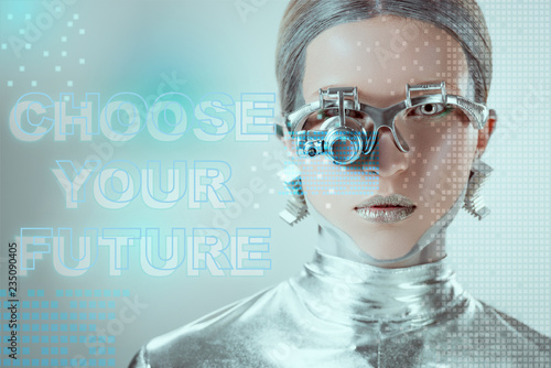 Photo  close-up view of silver robot with eye prosthesis looking at camera on grey with