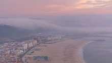 View Of Nazare Panorama With Cabins Of Funicular Timelapse. Fog Coming From Ocean At Evening During Sunset.