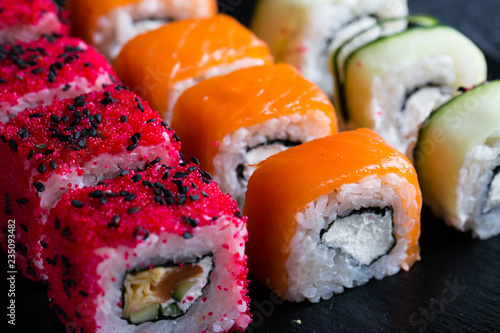 A variety of sushi and rolls on a dark background