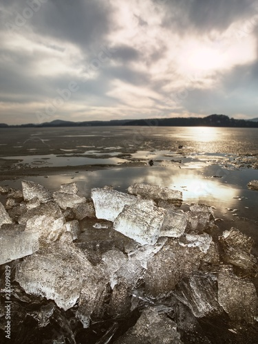 Frozen beach in cold winters day with colorful ice floe. Frozen icy waves covered rocks