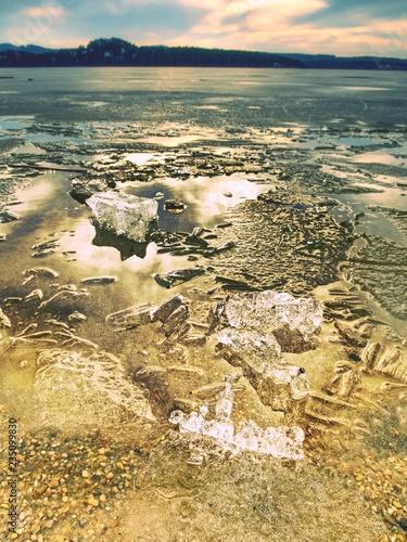 Ice fragments on empty sandy coast. Frozen sand on river coast.