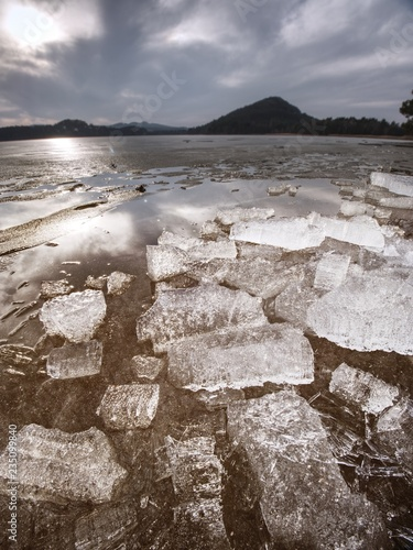 Ice fragments on the lake. Flat surface of frozen lake