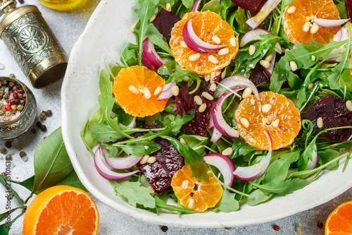 gourmet salad of arugula, baked beetroot, tangerines and red onions with spices and pine nuts in a white dish. Olive oil and ingredients on a grey surface. Selective focus