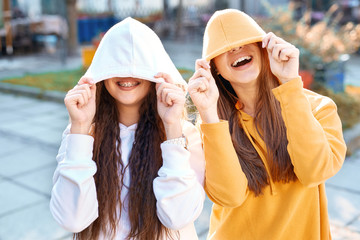 two young girls walking city having fun. joyful Women in bright colored hoodies walking, laughing and posing on the street, pulling the hoods over the heads