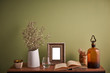 decorative home object white vase dry flower frame and book with green wall.