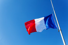 Lowered To Half-staff Flag Of France Over Blue Sky