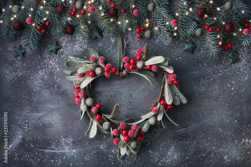 Foto op Plexiglas Kerstmis Heart-shaped mistletoe Christmas wreath and festive garland made from fir twigs, frosted berries and trinkets