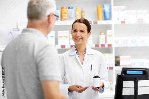 Poster Pharmacie medicine, pharmaceutics, healthcare and people concept - apothecary showing drug to senior male customer at drugstore