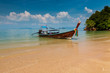 A traditional Longtail boat anchored next to a beautiful sandy beach on an island in Thailand