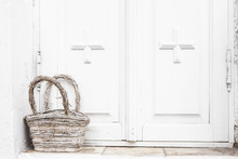 Old And White-washed Wicker Basket On A Background Of Rustic White Wooden Doors. Light White Background.
