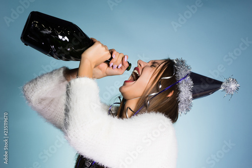 funny drunk young girl celebrating the new year, drinking champagne from the bot Wallpaper Mural