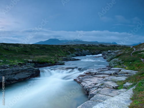 Photographie  River with hills and rocks in cloudy weather, Rondane National Park, Norway