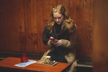 Woman Using Mobile Phone In Cafe