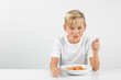 little blond boy in front of white background eats spaghetti