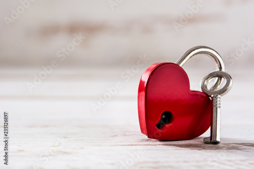 Photographie  Red padlock hearts with key on white wooden background. Copyspace