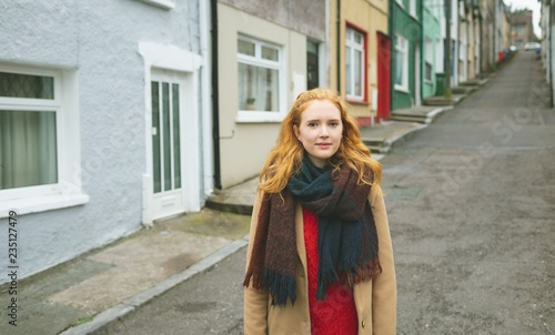 Portrait of young woman with blond hair and scarf standing in alley