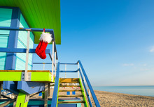 Santa Stocking Christmas Decoration Hanging From Brightly Colored Lifeguard Tower Next To Calm Tropical Seas In Miami Beach, Florida, USA