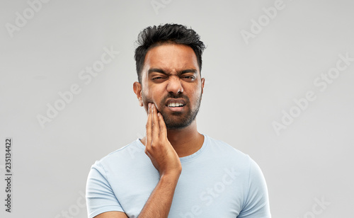 Fotografia  people, dentistry and health problem concept - indian man suffering from toothac