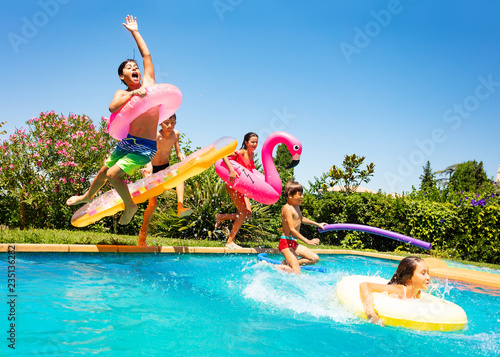 Fotografia Happy friends jumping in pool on the vacations