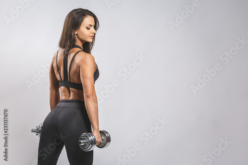 Fotografía  Brutal athletic woman pumping up muscles with dumbbells isolated over white background