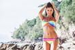 Woman in rainbow bikini on beach